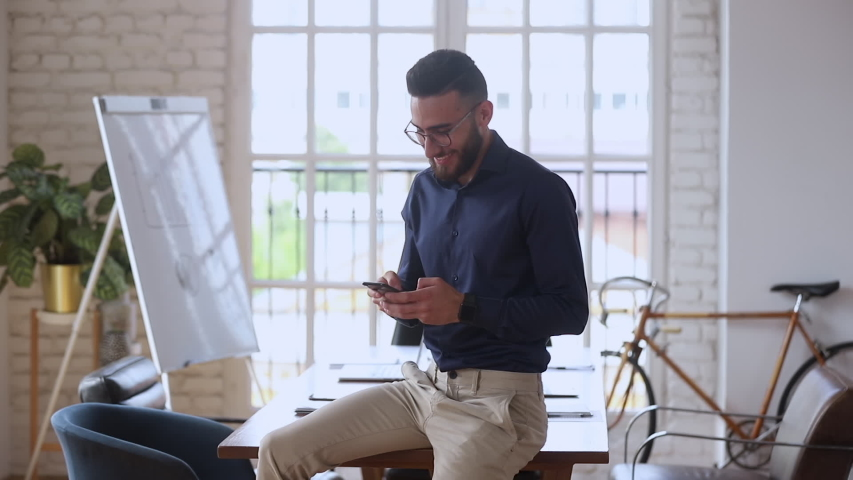 Smiling young businessman entrepreneur using smartphone mobile apps in modern creative office, happy male business owner holding phone texting sms message at work, professional technology concept Royalty-Free Stock Footage #1034217698