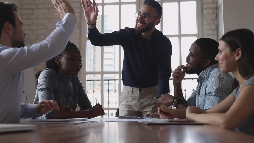 Happy male executives give high five at group meeting express effective solution business agreement partnership, friendly colleagues celebrate successful good teamwork result at diverse team briefing Royalty-Free Stock Footage #1034217758