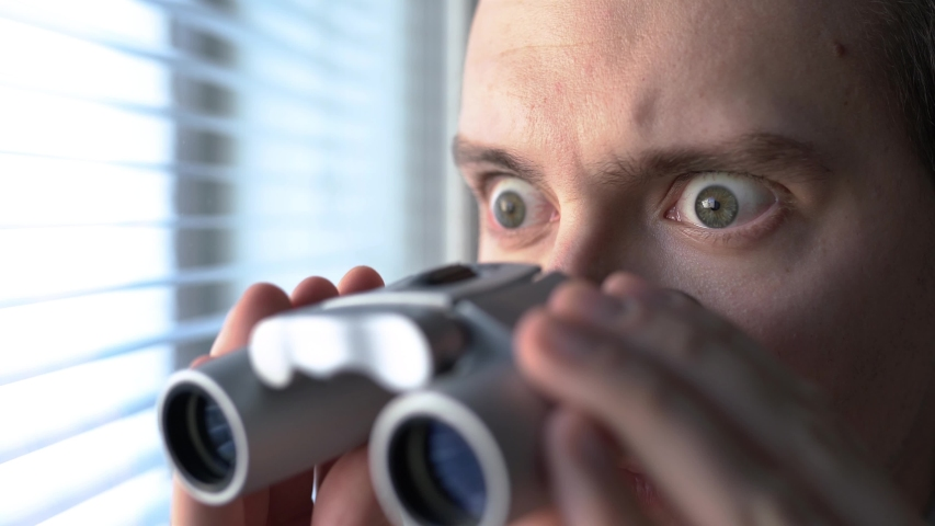 Surprised man with binoculars. Curious guy with big eyes. Nosy neighbour stalking or snooping secrets, gossip and rumour. Silly funny face. Shocked about unbelievable news. Stalker peeping people. | Shutterstock HD Video #1034221085