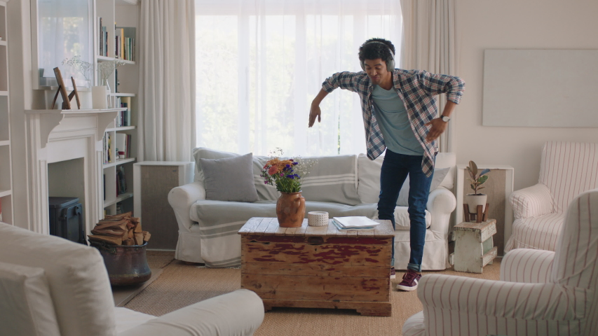 happy young man dancing at home celebrating success listening to music wearing headphones having fun dance in living room on weekend #1034230154