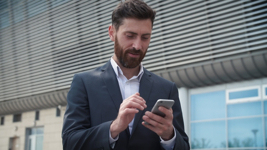 CloseUp of Attractive Young Businessman using his Smartphone and Smiles. He's texting Messages while standing near Modern Office Building. Wearing Classical Suit. Social Network. Apps. Smartphones. | Shutterstock HD Video #1034231681