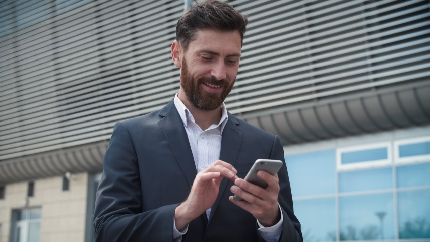 CloseUp of Attractive Young Businessman using his Smartphone and Smiles. He's texting Messages while standing near Modern Office Building. Wearing Classical Suit. Social Network. Apps. Smartphones.