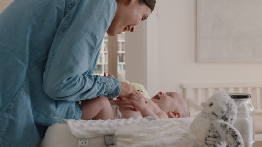 mother changing baby diaper at home caring for happy newborn infant loving mom cleaning childs nappy moisturizing skin enjoying motherhood childcare Royalty-Free Stock Footage #1034234855