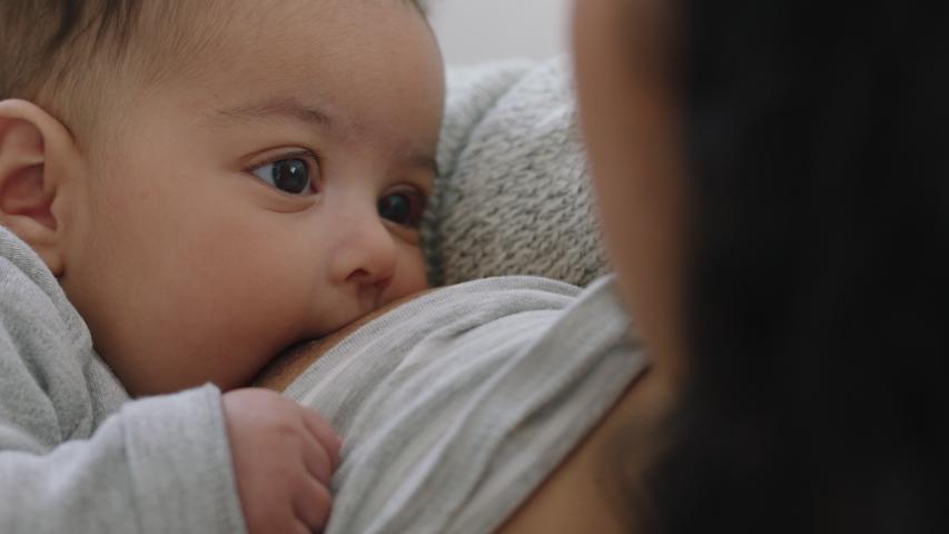 Mother breastfeeding baby at home mom nursing infant nurturing child suckling milk from breast motherhood maternity care