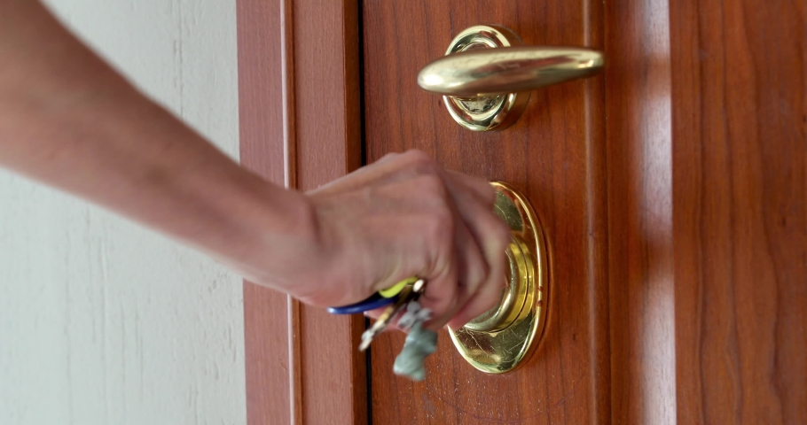 Woman using a key to open the lock of the front door | Shutterstock HD Video #1034237852