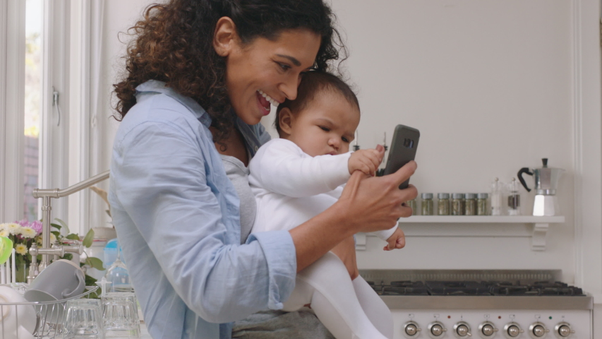 happy mother and baby having video chat using smartphone mom holding toddler enjoying mobile technology sharing motherhood lifestyle with friend on social media Royalty-Free Stock Footage #1034239076