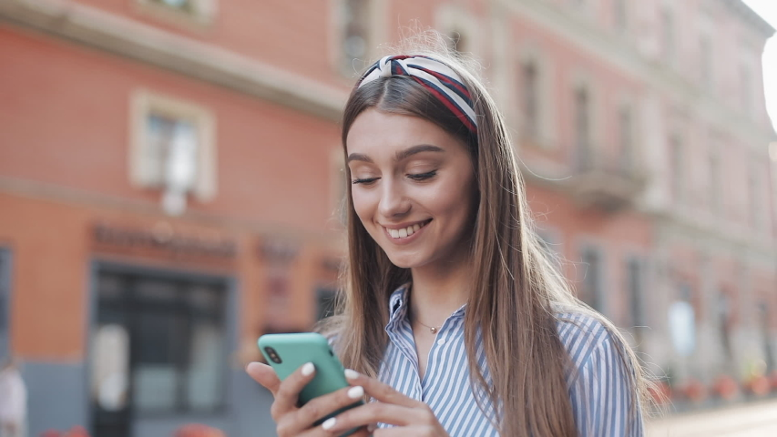 Cute woman wearing in blue and white striped dress using app on smartphone standing on the old city street. Beautiful girl having good news on smartphone. | Shutterstock HD Video #1034246948