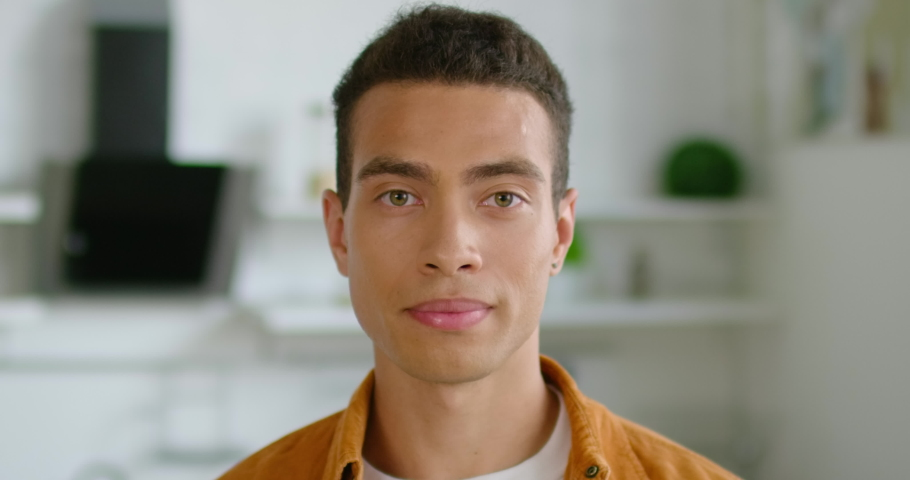 Portrait of young confident Hispanic man, close up, smiling, looking at camera, optimistic, decisive, healthy, handsome, enjoying his life, dark brown hair, brown eyes, Latin. 4K, shot on RED camera. | Shutterstock HD Video #1034256068