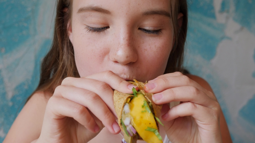 Teenager cute girl portrait face eating tasty tacos food in mexican cuisine restaurant