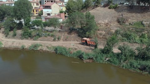 Excavator and truck working on the river for the consolidation of the bridge