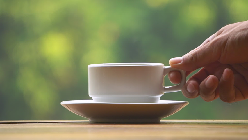 Close-up of hand placing hot ceramic white coffee cup with smoke on saucer over wooden table in nature green background #1034283953