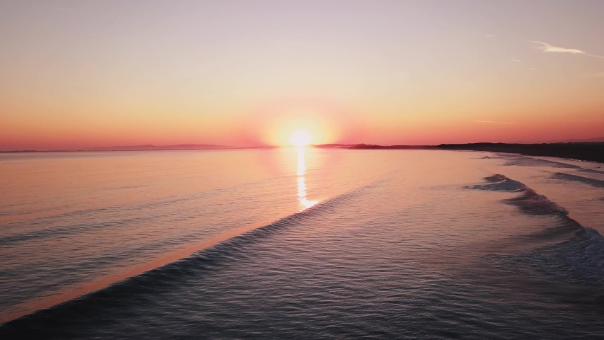 Aerial view sunset over sea, ocean waves crashing on beach   Shutterstock HD Video #1034285936