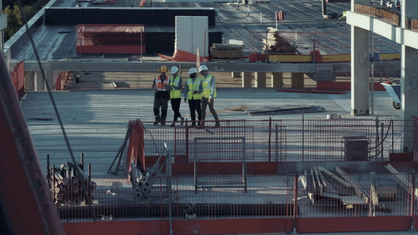 Aerial View: Diverse Team of Specialists Talking On the Roof Commercial, Industrial Building / Skyscraper Formwork Construction Site. Real Estate Project Civil Engineer, Investor, Architect and Worker