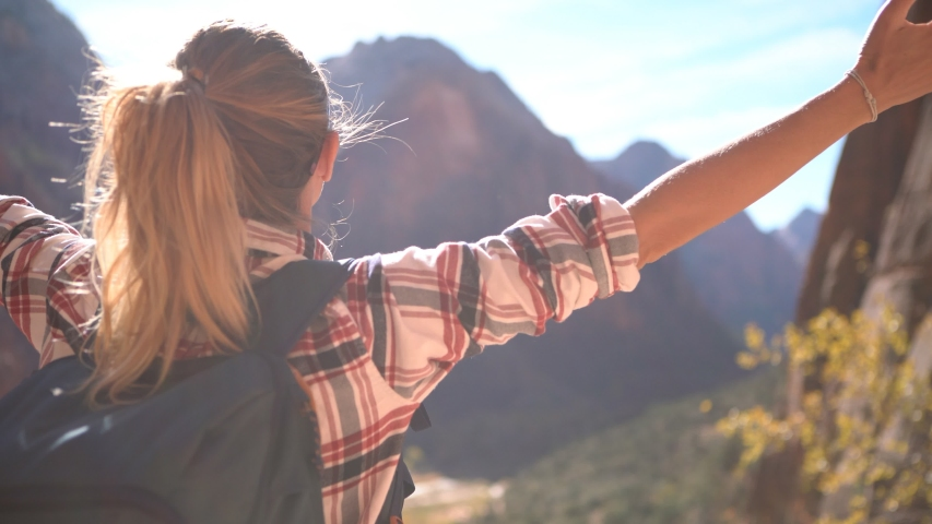 Cheerful young work man on top of canyon arms outstretched embracing nature and enjoying life; hiking girl loving exploring national p | Shutterstock HD Video #1034291321