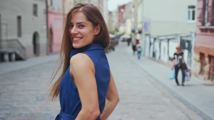Appealing girl looking on camera walking backwards in the street. Outdoor portrait happy female tourist having good time wandering around town in summer. | Shutterstock HD Video #1034296325