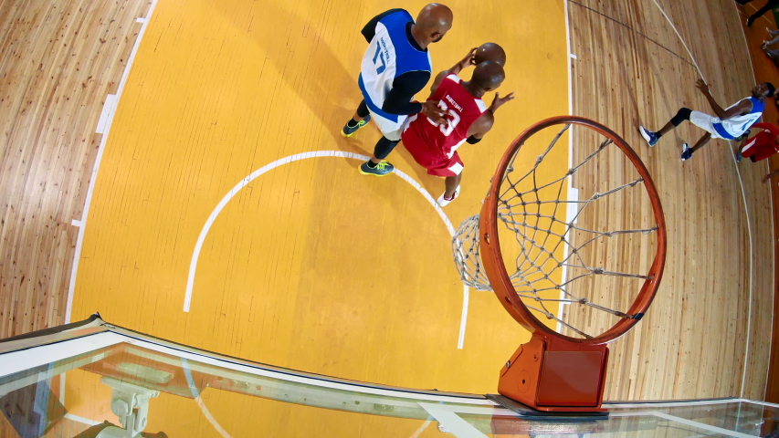 High angle of professional basketball player in action performing slam dun in a basketball hoop on a sports arena