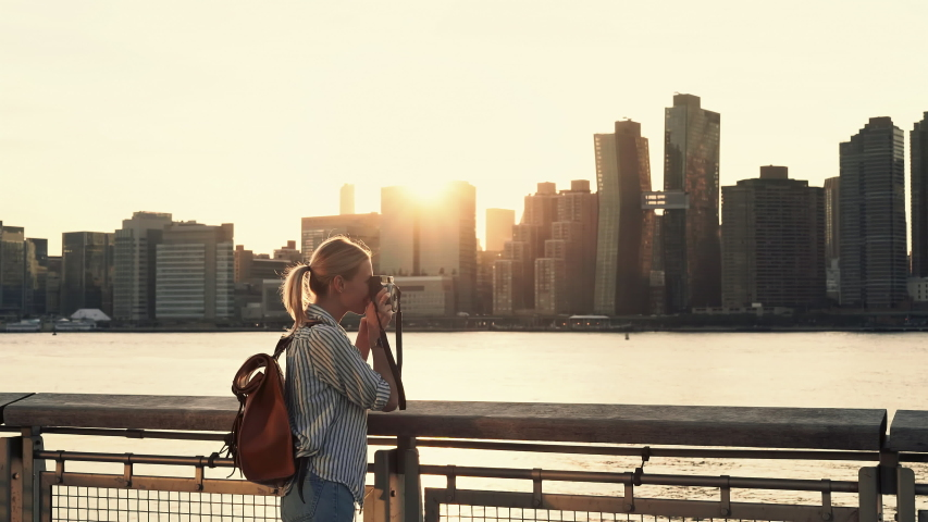 Hipster girl photographing scenic landmark of Manhattan island via film instant camera looking at made image and clicking photo with smartphone application for sharing to travel website