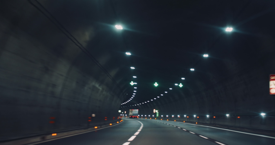 Driving a car in the city at night through wide illuminated tunnel. Following a truck speeding on highway. Slow motion.
