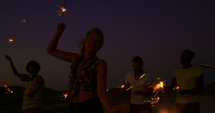 Close up of a young Caucasian woman on a beach at dusk with her friends, jumping around and having fun, waving glowing sparklers. Summer Sunset Party on the beach with friends having fun 4k