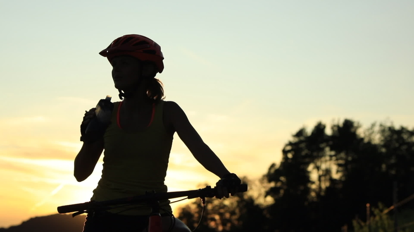 Pretty, young female biker outdoors on her mountain bike on a sunset, drinking water   Shutterstock HD Video #1034364437