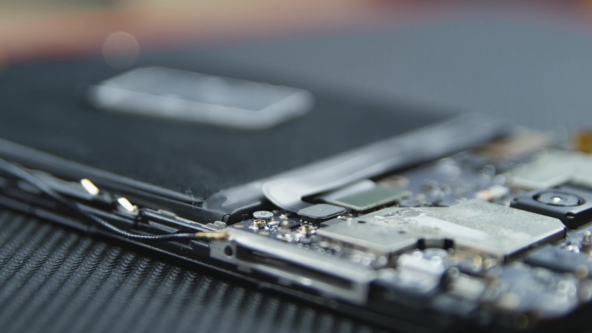 Close-up shot showing the process of cell phone repairing. Hands of repairer getting out the screws with a screwdriver. The internal components of a smartphone. Disassembled cell phone.  Royalty-Free Stock Footage #1034367941
