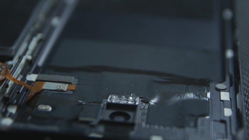 Close-up of a cell phone repair. The internal components of a smartphone. Disassembled cell phone. Cell Phone Battery. Master disassembled mobile device for detail. Chips and details of the smartphone Royalty-Free Stock Footage #1034367980