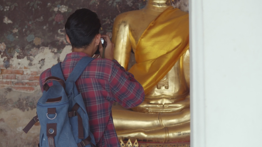 Portrait of handsome young Asian man tourists walking traveling and using film camera taking a photo in temple Thailand. Asian man blogger happy enjoying leisure lifestyle travel. | Shutterstock HD Video #1034376389