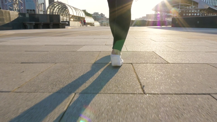 Female legs in black trousers and white shoes walk along a clean, empty path. towards the sun, shooting from a low point, the camera follows the movement. city walk in slow motion close up   Shutterstock HD Video #1034379119