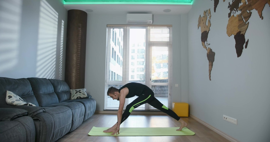 Indoor shot of handsome young man in sportwear practicing yoga on a mat in living room at home. Cozy spacious room and pleasant atmosphere. 4K video | Shutterstock HD Video #1034382761