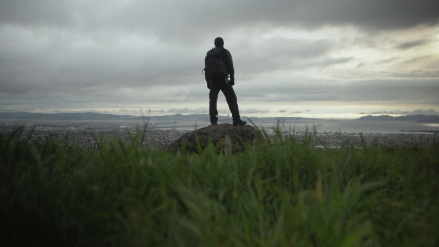 A photographer proudly stands on a cliff with an incredible view of the city and sunset on a beautiful cloudy evening.  Shot in 4K UHD resolution. | Shutterstock HD Video #1034396177