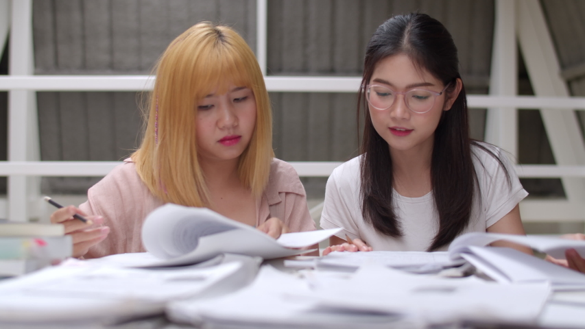 Asian student women do project in library at university. Group of young friends undergraduate girl looking books for information and knowledge on lecture desk at college campus concept. Slow motion. Royalty-Free Stock Footage #1034405492