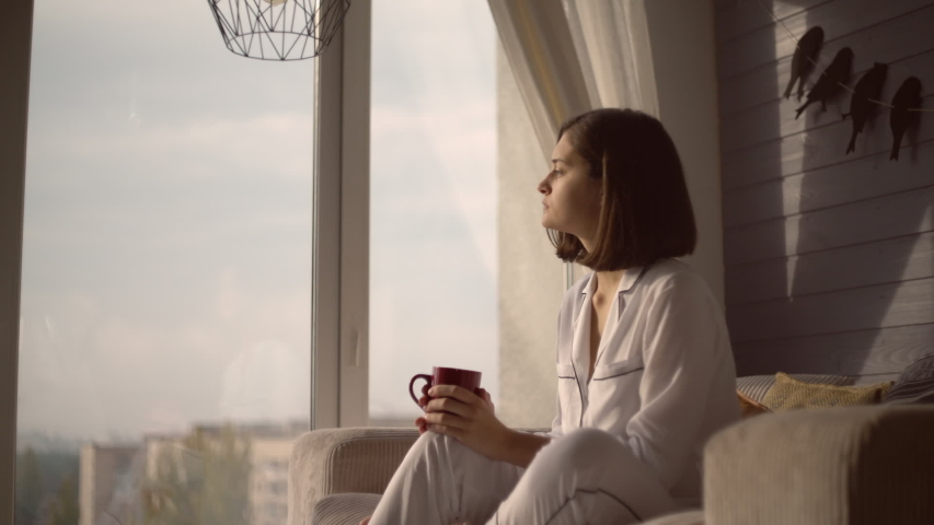 Attractive girl looks out the window at cosy flat. Portrait woman sitting near the big window holding red mug. Lady wearing in white pajamas sits in chair looking on the street and thinking.