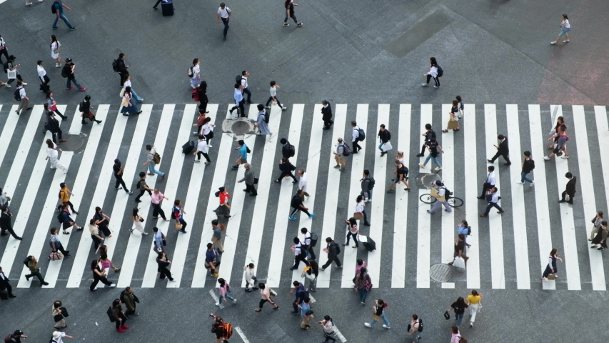 Aerial view of pedestrians walk at Shibuya Crossing. The scramble crosswalk is one of the largest in the world. Shibuya, Tokyo, Japan.
