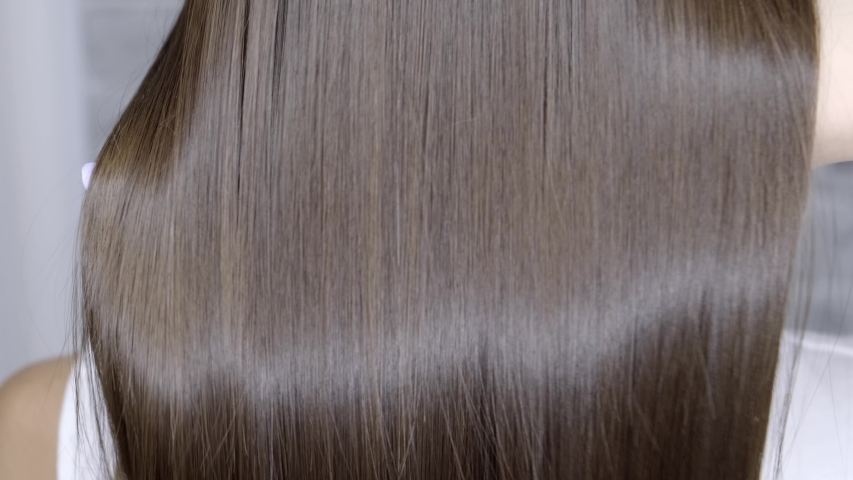 Result after lamination and hair straightening in a beauty salon for a girl with brown hair. hair care concept. Royalty-Free Stock Footage #1034425973