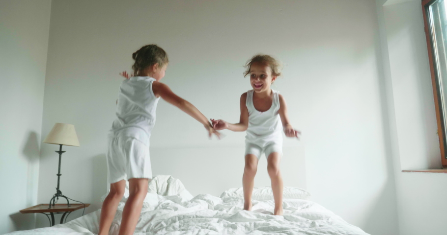 Authentic slow motion shot of two little girls sisters in white pajamas are having fun to jump on the bed of their parents bedroom.