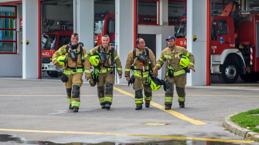 Four firefighters have finished with their practise. They look exhausted and their faces are a bit dirty.   Shutterstock HD Video #1034434544