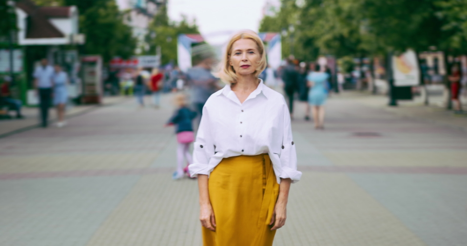 Time lapse portrait of beautiful mature lady with serious face in city street standing alone looking at camera. Summer town, people and modern life concept.