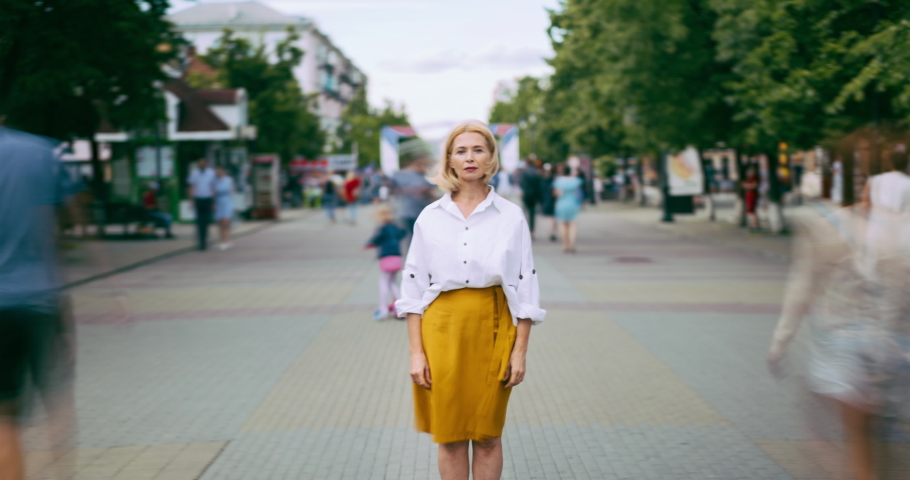 Zoom in time lapse of attractive mature blonde standing in city street on summer day looking at camera alone. Modern lifestyle, people and society concept.