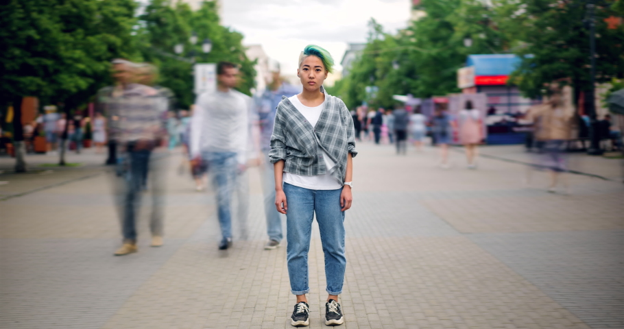 Time lapse of Asian teenage hipster standing in city center in busy street looking at camera wearing trendy clothes while crowds of people are walking by.