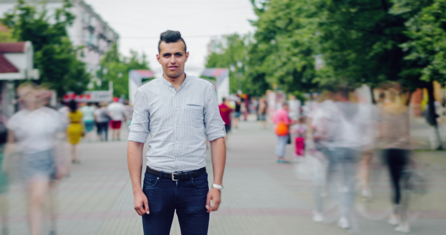 Time lapse of serious mixed race man standing alone in busy pedestrian street in city looking at camera while crowd of people is passing around. Youth and life concept.