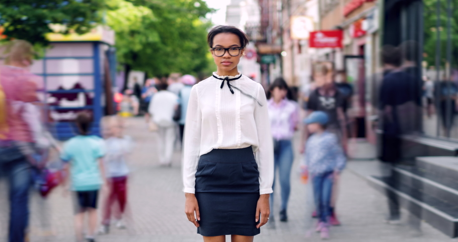 Time lapse of mixed race teenage girl standing in pedestrian street with serious face wearing elegant clothes while young men and women are rushing around.