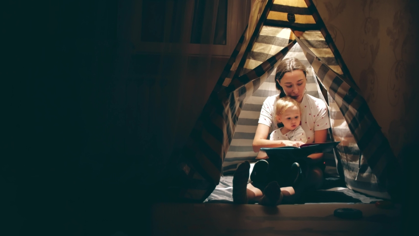 Mum and her little daughter read a book together in a teepee in the evening | Shutterstock HD Video #1034441375