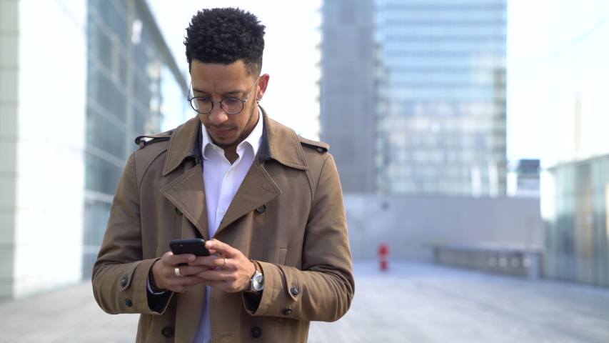 Medium shot of a thoughtful businessman texting on smartphone while standing outside the office building #1034456540