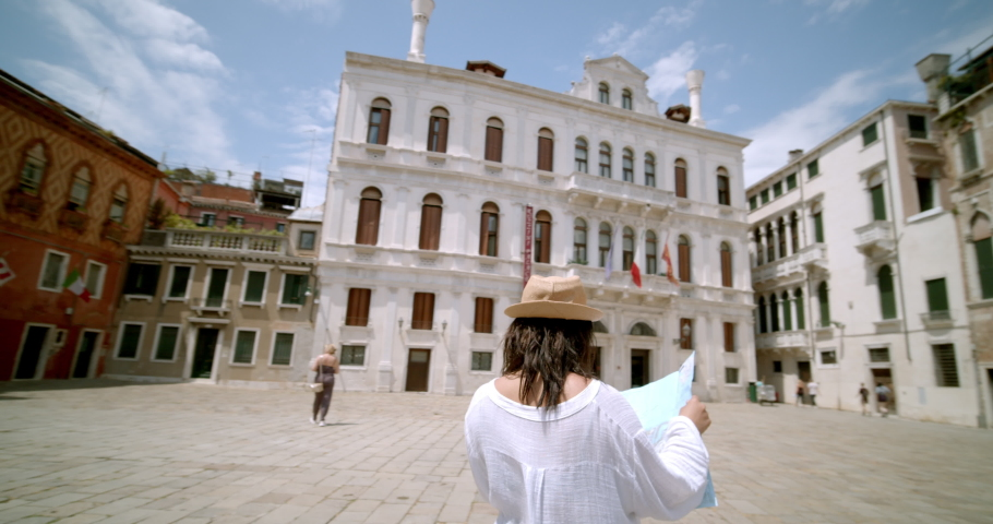 Female traveller reading street signs and map looking lost trying to find her way wearing fedora travelling abroad standing in Italian square in Venice Italy | Shutterstock HD Video #1034464016