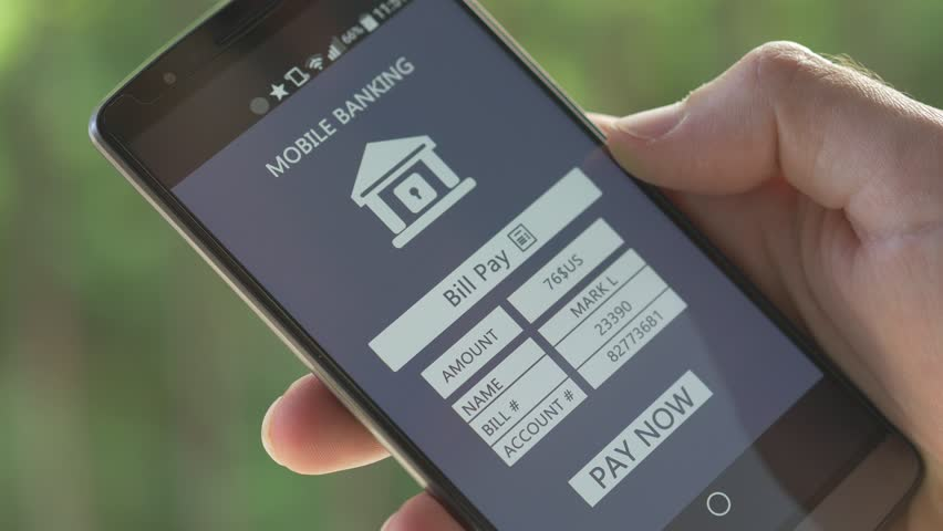 Paying a store or provider bill is now possible directly from a smartphone. The finger is pressing the button to accept to pay with the mobile banking application. | Shutterstock HD Video #10344722