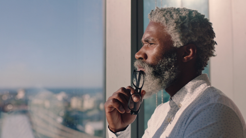 mature african american businessman looking out window planning ahead thinking of ideas for future business development with view of city at sunset 4k Royalty-Free Stock Footage #1034473316