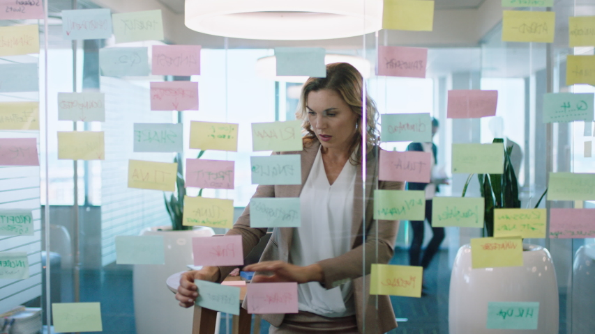 beautiful business woman using sticky notes brainstorming ideas planning strategy problem solving with creative mind map working on solution in office 4k