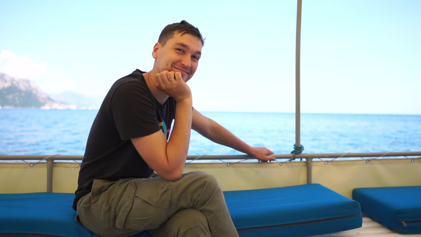 Man is on a boat, sits with his head propped on his hand, and shows a gesture ok | Shutterstock HD Video #1034473697