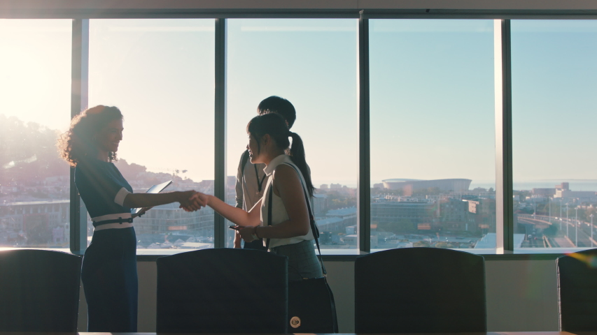 business people shaking hands consultant greeting international clients with handshake planning partnership deal female executive meeting shareholders in corporate office at sunset Royalty-Free Stock Footage #1034474585