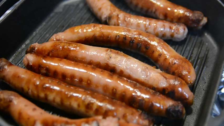 Delicious grilled pork sausages rollin on hot grill pan | Shutterstock HD Video #1034475032